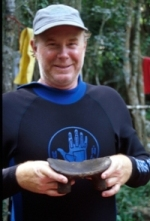 "John Foster holding a carved wooden stool or ""duho."""