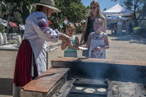 docent serving tortillas to visitors