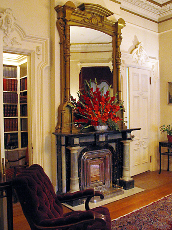 Fireplace and mirror in library/music room.
