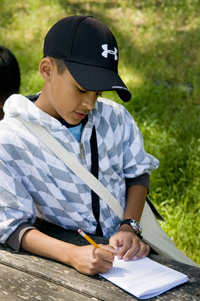 Boy recording observations in a park
