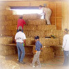 Volunteers assisting in the placing of straw bales for a historical structure.