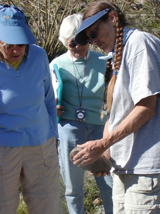 Stewards identify ground stone artifacts.
