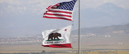 US and California flags in wind at Antelope Valley California Poppy Reserve SR