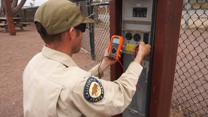 Parks worker using voltmeter